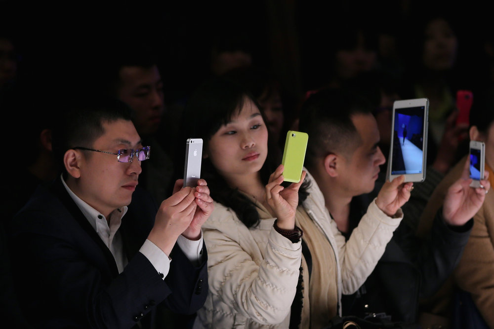 . Chinese people take photos with iPhone and iPad during Bosideng Down Wear Collection on the third day of Mercedes-Benz China Fashion Week Autumn/Winter 2013/2014  at 751 D.PARK Workshop on March 26, 2013 in Beijing, China.  (Photo by Feng Li/Getty Images)