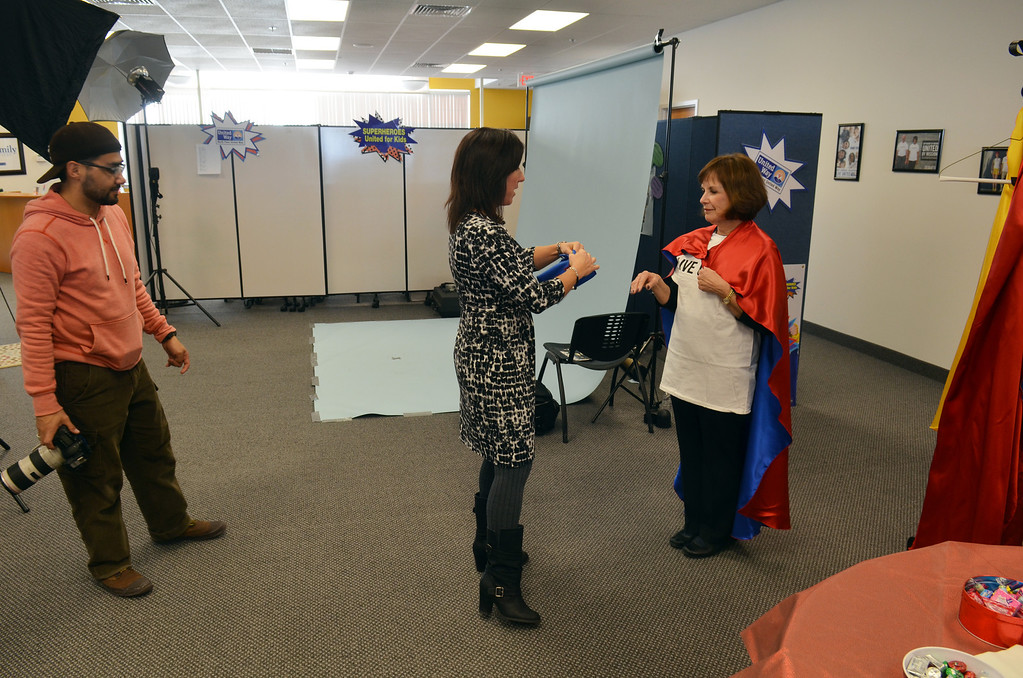 . Christy Holland, center, helps Debbie Levin from Montgomery County Community College prepare for a photo shoot for the North Penn United Way\'s third annual Superheroes United for Kids event.   Finished photographs are used in promotion and will be  displayed during the event in April.   Friday, January 24, 2014.  Photo by Geoff Patton