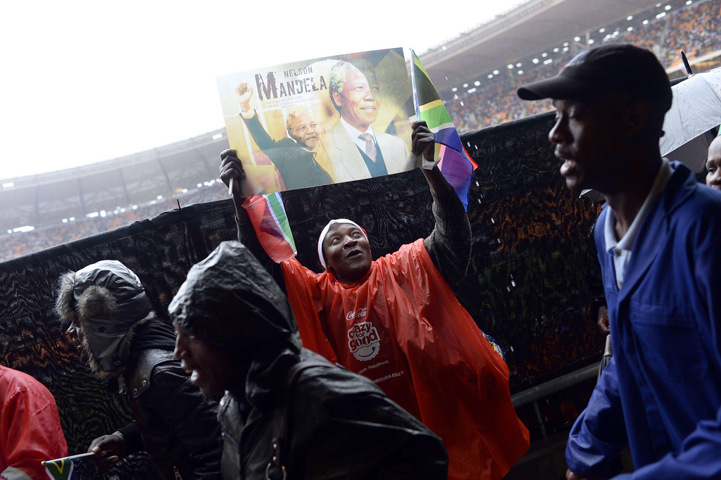 . A man holds a sign bearing pictures of late South-African president Nelson Mandela , on December 10, 2013 during the memorial service for Mandela at Soccer City Stadium in Johannesburg. Mandela, the revered icon of the anti-apartheid struggle in South Africa and one of the towering political figures of the 20th century, died in Johannesburg on December 5 at age 95. Mandela, who was elected South Africa\'s first black president after spending nearly three decades in prison, had been receiving treatment for a lung infection at his Johannesburg home since September, after three months in hospital in a critical state. PEDRO UGARTE/AFP/Getty Images