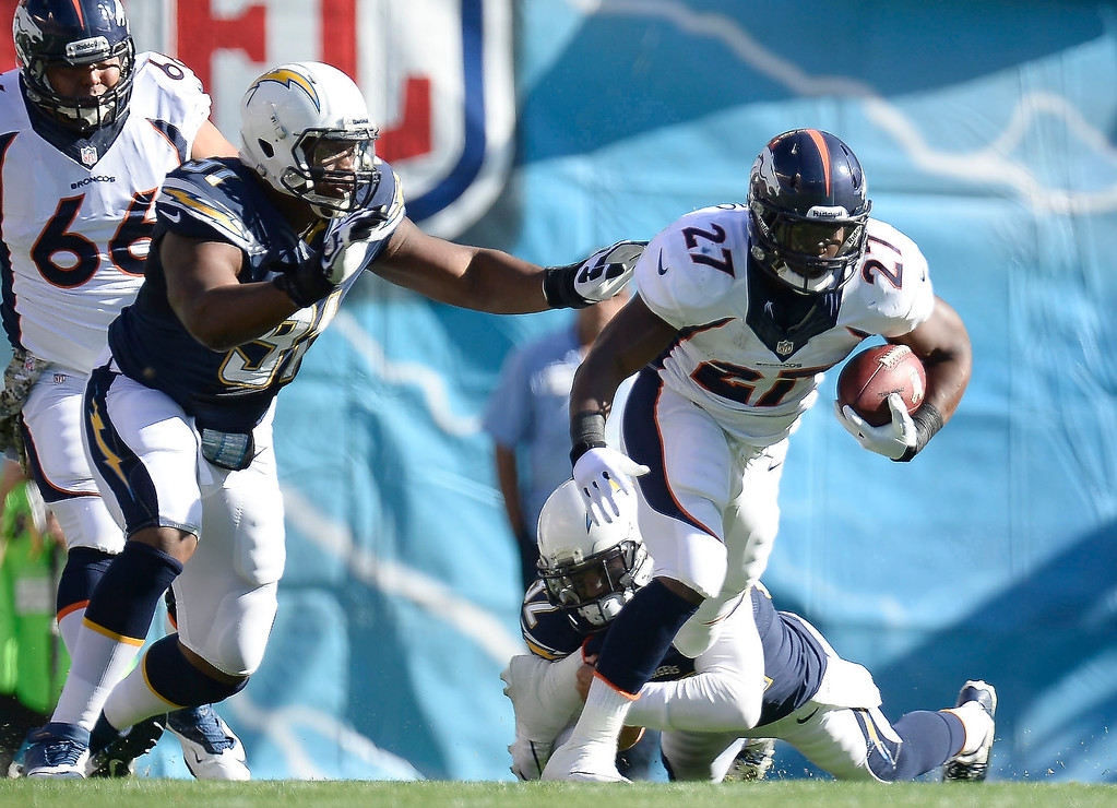 . Denver Broncos running back Knowshon Moreno (27) slips by a tackle by San Diego Chargers free safety Eric Weddle (32) as San Diego Chargers defensive end Kendall Reyes (91) comes in to get him from behind during the first quarter at Qualcomm Stadium. (Photo by John Leyba/The Denver Post)