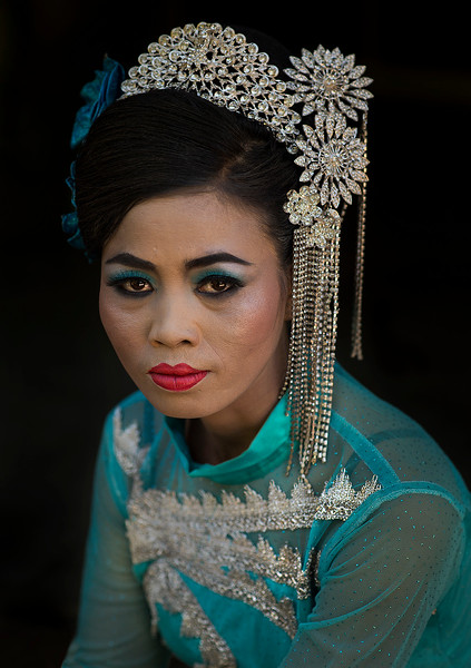 Portrait of a woman dressed in traditional clothing for her sons novice initiation ceremony.  Myanmar 2017