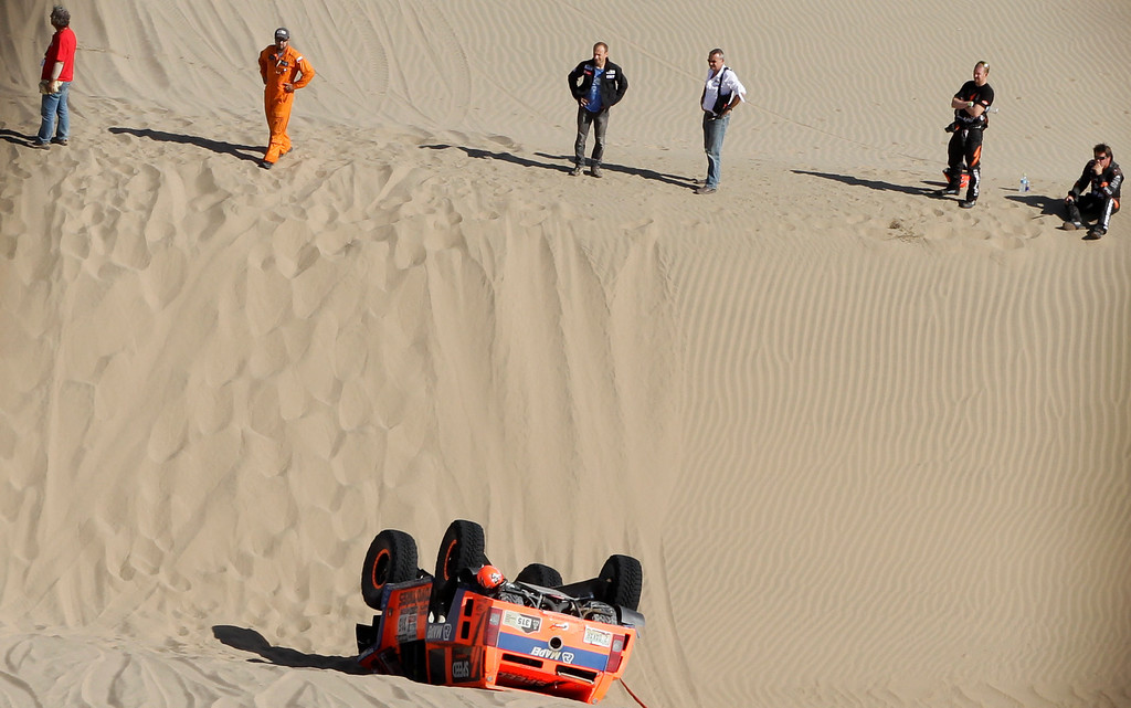 . Hummer driver Robby Gordon, right, and co-driver Kellon Walch, second from right, both of the U.S., stand on a dune overlooking their overturned vehicle during the 4nd stage of the 2013 Dakar Rally from Nazca to Arequipa, Peru, Tuesday, Jan. 8, 2013. The race finishes in Santiago, Chile, on Jan. 20. Third from right is Dakar rally director Etienne Lavigne. (AP Photo/Victor R. Caivano)