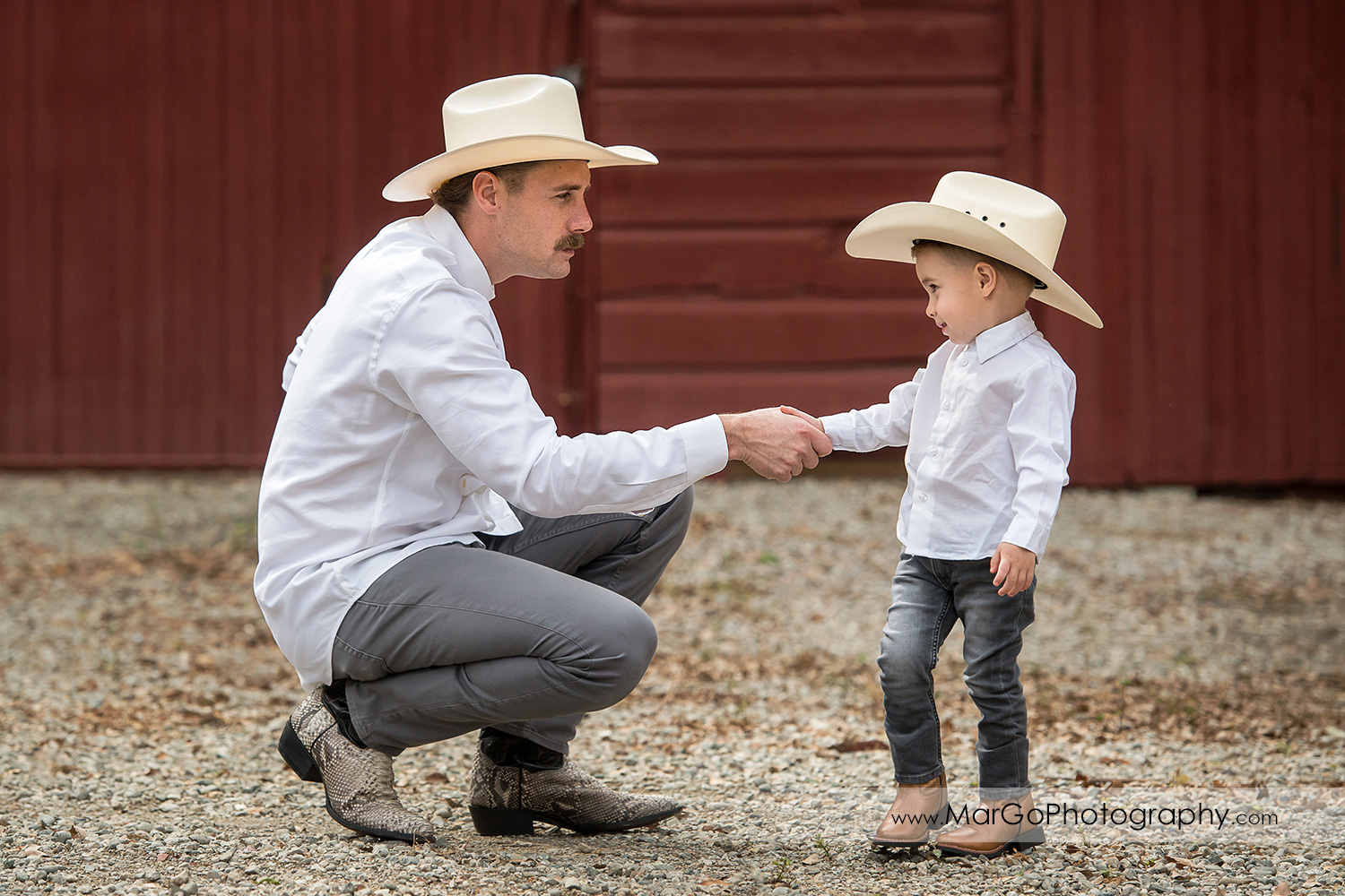 man and little boy in white shirts, gray jeans and cowboy hats shaking hands in front of red barn in Shinn Historical Park and Arboretum in Fremont