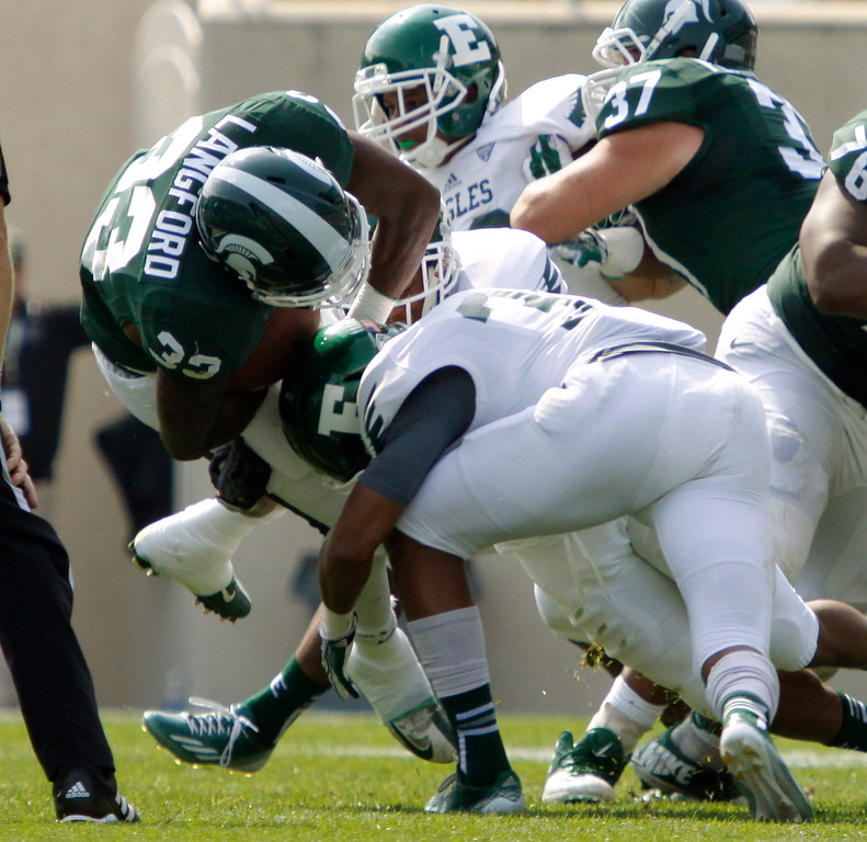 . Michigan State\'s Jeremy Langford (33) is upended by Eastern Michigan\'s Jason Beck during the first quarter of an NCAA college football game, Saturday, Sept. 20, 2014, in East Lansing, Mich. Michigan State won 73-14. (AP Photo/Al Goldis)