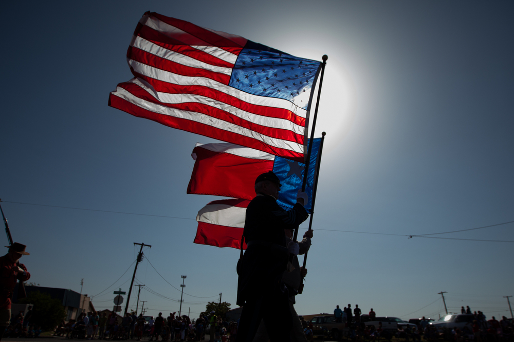 . The American flag and Texas state flag are carried during the 65th annual Jaycees Independence Day parade, Friday, July 4, 2014, in Odessa, Texas. (AP Photo/The Odessa American, Courtney Sacco)