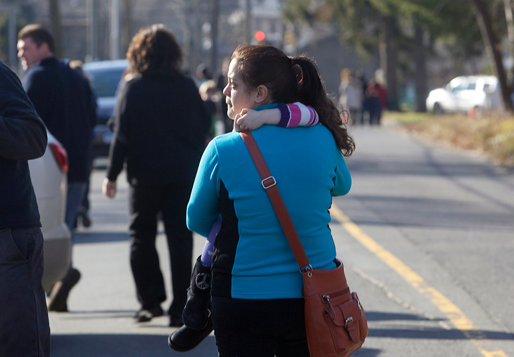 . A woman carries her daughter following a shooting at Sandy Hook Elementary School in Newtown, Connecticut, December 14, 2012. A shooter opened fire at the elementary school in Newtown, Connecticut, on Friday, killing several people including children, the Hartford Courant newspaper reported. REUTERS/Michelle McLoughlin