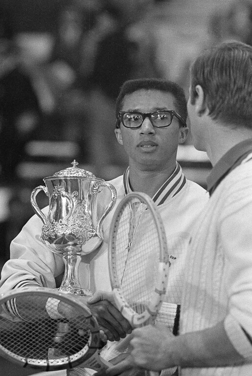 . Lieut. Arthur Ashe, left, holds onto the the Sugar Bowl tennis trophy as he is congratulated by Yugoslavian star Nicola Pilic after winning the singles tournament, 5-7, 8-10, 6-3, 11-9 and 6-3, in New Orleans, Dec. 30, 1967. Ashe, a native of Richmond, Va., is stationed at West Point.  (AP Photo/Charles Kelly)