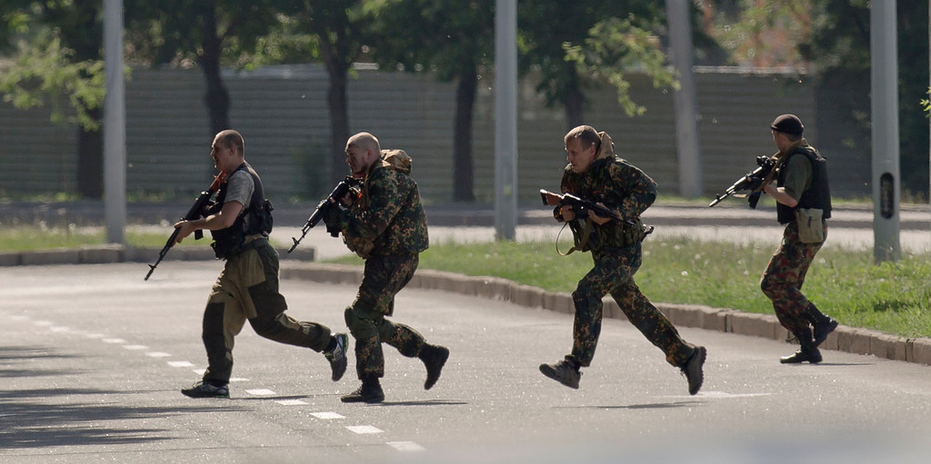 """. Pro-Russian gunmen take positions near the airport, outside Donetsk, Ukraine, on Monday, May 26, 2014. Ukraine\'s military launched air strikes Monday against separatists who had taken over the airport in the eastern capital of Donetsk, although exit polls from Sunday\'s first round of the new presidential election predict Petro Poroshenko will be elected president in this bitterly divided country, and he vowed \""""to bring peace to the Ukrainian land\"""".(AP Photo/Vadim Ghirda)"""