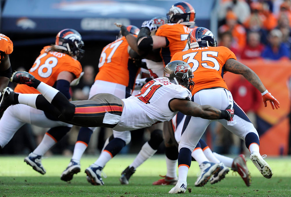 . Denver Broncos running back Lance Ball #35 breaks away from a tackle by Tampa Bay Buccaneers defensive end Da\'Quan Bowers #91 during the second quarter, The Denver Broncos vs The Tampa Bay Buccaneers at Sports Authority Field Sunday December 2, 2012. Tim Rasmussen, The Denver Post