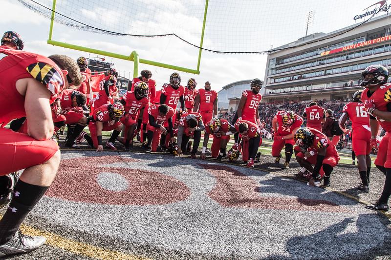 Maryland players take a knee at the memorial to #79 Jordan McNair.