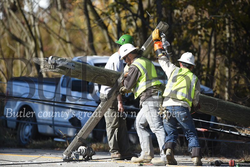 Harold Aughton/Butler Eagle: Utility workers remove a utility pole from the  scene of a one-vehicle accident at 892 Ekastown Road, Monday. According to PSP Trooper Sheppeck, the driver of a white, 2-door pickup truck was traveling west on Eakerstown Road, Monday, Oct. 28 when the driver lost control of his vehicle striking a utility pole.  It took emergency workers more than an hour to reach the driver as utility workers had to shut down power before removing wires from the vehicle. The driver walked out of the truck on his own power. According to the Trooper Sheppeck, the driver was only wearing the lap strap of this seatbelt and hit his head on the windshield. Rescue personnel from the Butler Ambulance Service transported the driver to the hospital with non-life threatening injuries.