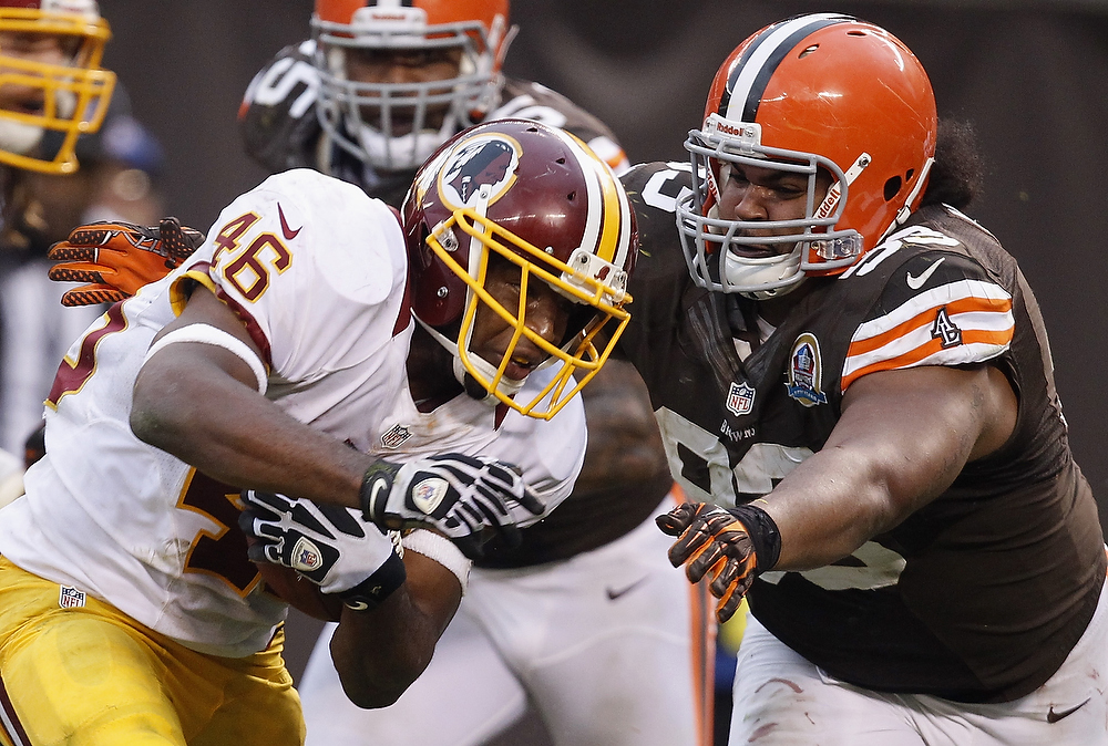 . Running back Alfred Morris #46 of the Washington Redskins runs the ball by defensive lineman John Hughes #93 of the Cleveland Browns at Cleveland Browns Stadium on December 16, 2012 in Cleveland, Ohio.  (Photo by Matt Sullivan/Getty Images)