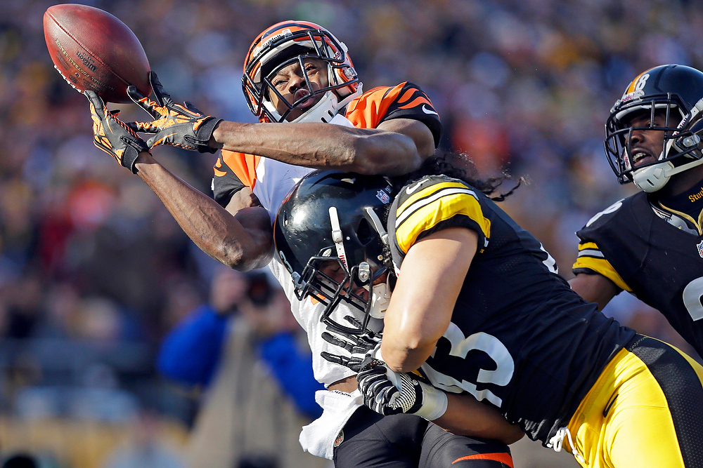 . Cincinnati Bengals wide receiver A.J. Green (18) is hit by Pittsburgh Steelers strong safety Troy Polamalu (43) as he tries to catch a pass in the second quarter of an NFL football game in Pittsburgh, Sunday, Dec 23, 2012. The pass was incomplete. (AP Photo/Gene J. Puskar)