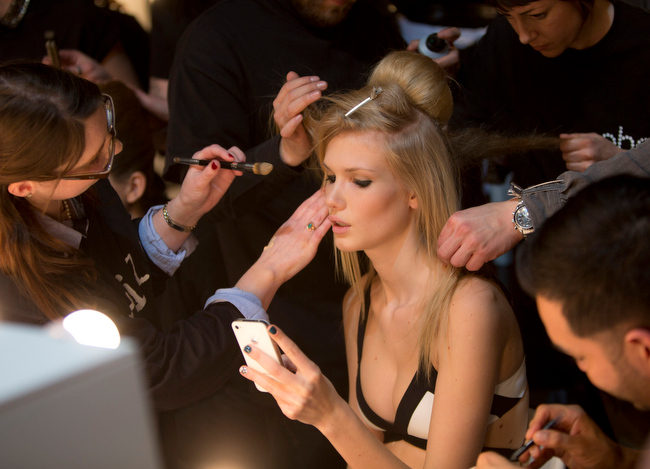 . A model\'s makeup is applied and her hair brushed, as she is busy working her phone, backstage ahead of the PPQ Autumn/Winter 2013 collection during London Fashion Week, Friday, Feb. 15, 2013, at Somerset House in central London. (Photo by Joel Ryan/Invision/AP)