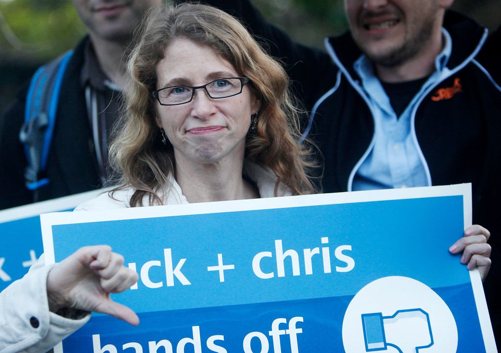 """. Robyn Erler gives a thumbs down during a protest in front of the house of Facebook CEO Mark Zuckerberg in Palo Alto on Wednesday, Feb. 13, 2013. About 40 protesters rallied in front of Zuckerberg�s home as the co-founder of Facebook hosted a campaign fundraiser for New Jersey Republican Gov. Chris Christie. The protesters said they objected to Christie�s visit because of his efforts to strip funding from Planned Parenthood and other women�s reproductive health care programs. Protester and Palo Alto resident Cheryl Lilienstein said she wondered whether Zuckerberg had any idea what Planned Parenthood means for women\'s health or what Christie�s stances are. \""""I hope he\'s just confused,\"""" she said. Zuckerberg and wife Priscilla Chan first got to know Christie after donating $100 million to struggling Newark, N.J., schools two years ago, according to a Facebook spokeswoman.  (Kirstina Sangsahachart/ Daily News)"""