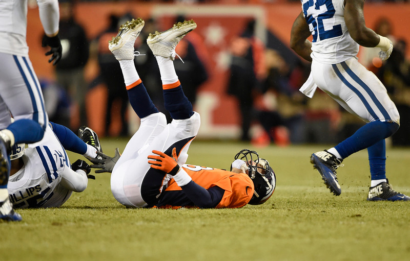 . Peyton Manning (18) of the Denver Broncos is knocked down by Shaun Phillips (55) of the Indianapolis Colts in the fourth quarter. The Denver Broncos played the Indianapolis Colts in an AFC divisional playoff game at Sports Authority Field at Mile High in Denver on January 11, 2015. (Photo by Joe Amon/The Denver Post)