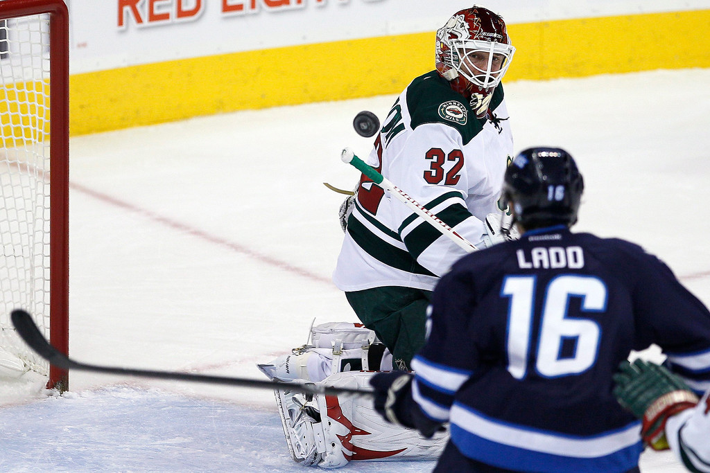 . Minnesota Wild\'s goaltender Niklas Backstrom (32) and Winnipeg Jets\' Andrew Ladd (16) keep their eyes on the rebound during the first period of an NHL game in Winnipeg, Manitoba, Saturday, Nov. 23, 2013. (AP Photo/The Canadian Press, John Woods)