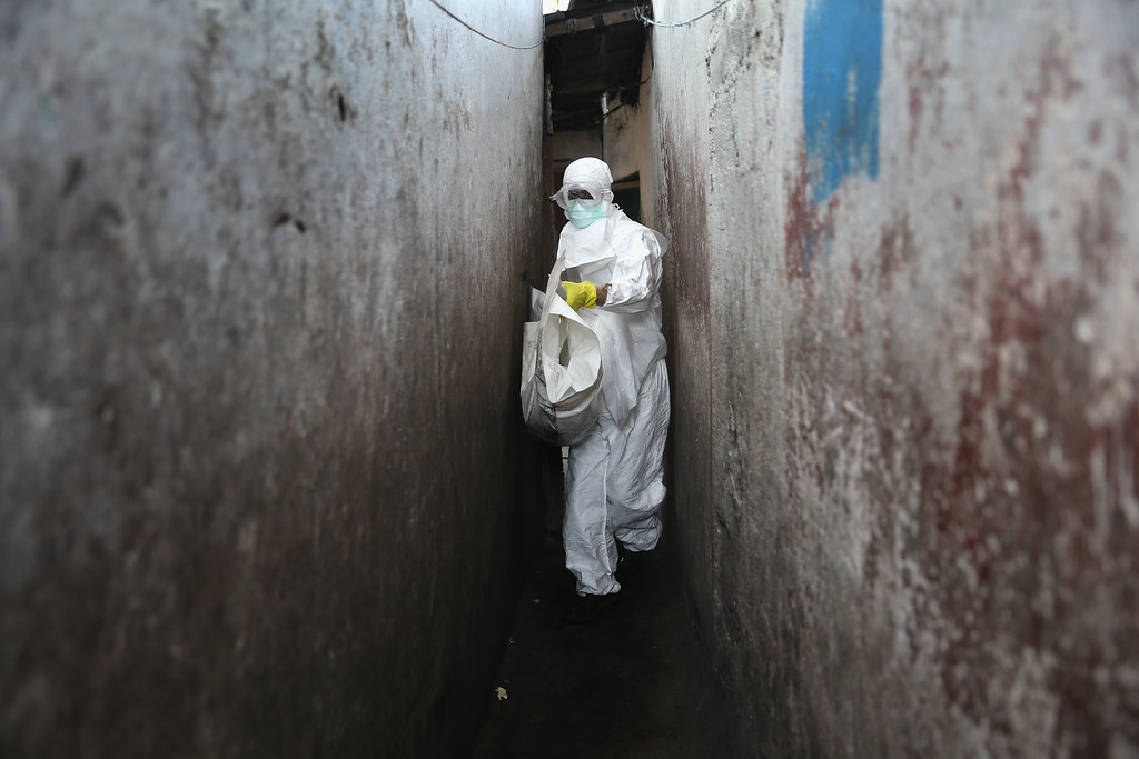 ". A Liberian Red Cross burial team in Ebola protectant clothing collects the body of a toddler from a home in the West Point township on January 28, 2015 in Monrovia, Liberia. They took a swab sample to test for Ebola. They were to deliver the body to a new ""safe burial\"" cemetery, operated by USAID-funded Global Communities, where almost 300 people have been interred in its first month of operation. Increasingly fewer of the bodies have come from Ebola Treatment Units (ETUs), as Ebola infection rates decline. The cemetery, where burial team members wear protective clothing, (PPE), has been seen in Monrovia as a major achievement, as families of the deceased are permitted to view the burials, important in Liberian culture. In an effort to control the Ebola epidemic in 2014, the Liberian government had ordered the cremation of all deceased in the capital, often further traumatizing surviving family members and unintentionally encouraging many families to hide their dead for secret burials.  (Photo by John Moore/Getty Images)"