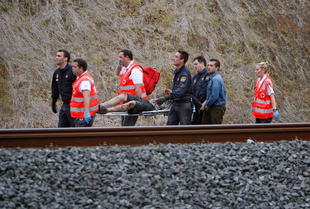 . A man is evacuated by emergency personnel at the scene of a train derailment in Santiago de Compostela, Spain, on Wednesday, July 24, 2013.  (AP Photo/ El correo Gallego/Antonio Hernandez)
