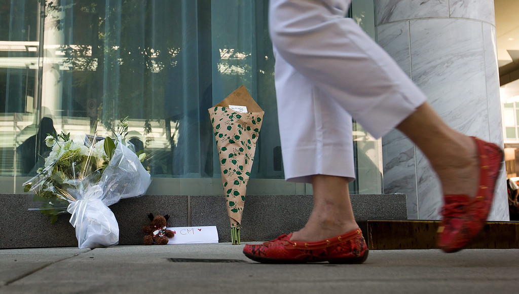 . A woman walks past a small memorial on Sunday, July 14, 2013, for Canadian actor Cory Monteith outside the Fairmont Pacific Rim Hotel where he died on Saturday, in Vancouver, British Columbia. Monteith\'s body was found in a room at the hotel Saturday. (AP Photo/The Canadian Press, Darryl Dyck)