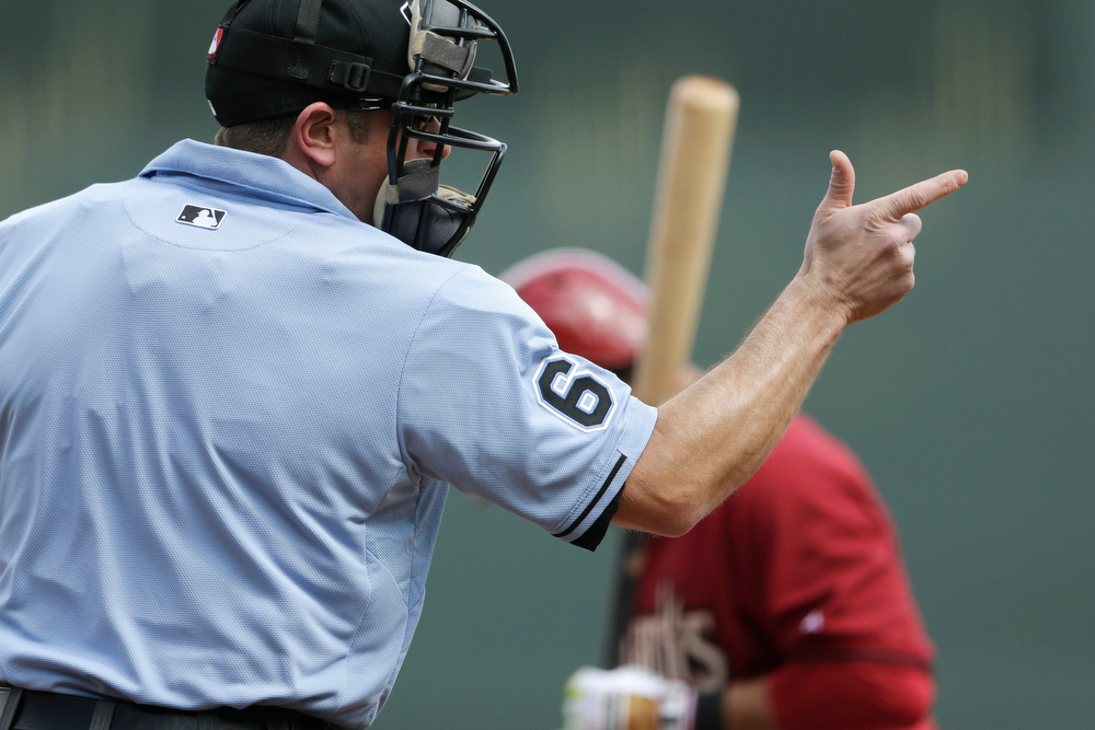 . Umpire Chris Guccione calls a strike as Arizona Diamondbacks\' Gerardo Parra bats against Colorado Rockies pitcher Franklin Morales during the first inning of a spring training baseball game Friday, Feb. 28, 2014, in Scottsdale, Ariz. (AP Photo/Gregory Bull)