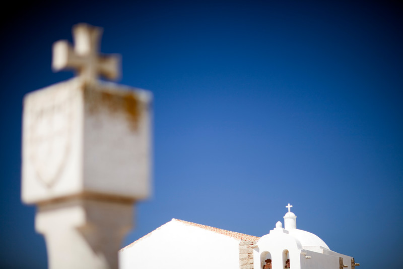 Stone cross with the Portuguese national emblem and Nossa Senhora da Graça church, fortress of the town of Sagres, municipality of Vila do Bispo, district of Faro, region of Algarve, southwestern Portugal