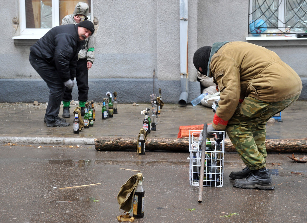 """. Pro-Russia activists prepare  Molotov cocktails as they guard a barricade outside a regional police building seized by armed separatists in Slavyansk on April 13, 2014. Ukraine on Sunday launched an \""""anti-terrorist operation\"""" in the eastern town of Slavyansk, where pro-Russian gunmen have seized police and security services buildings, Interior Minister Arsen Avakov said. AFP PHOTO / GENYA SAVILOV"""