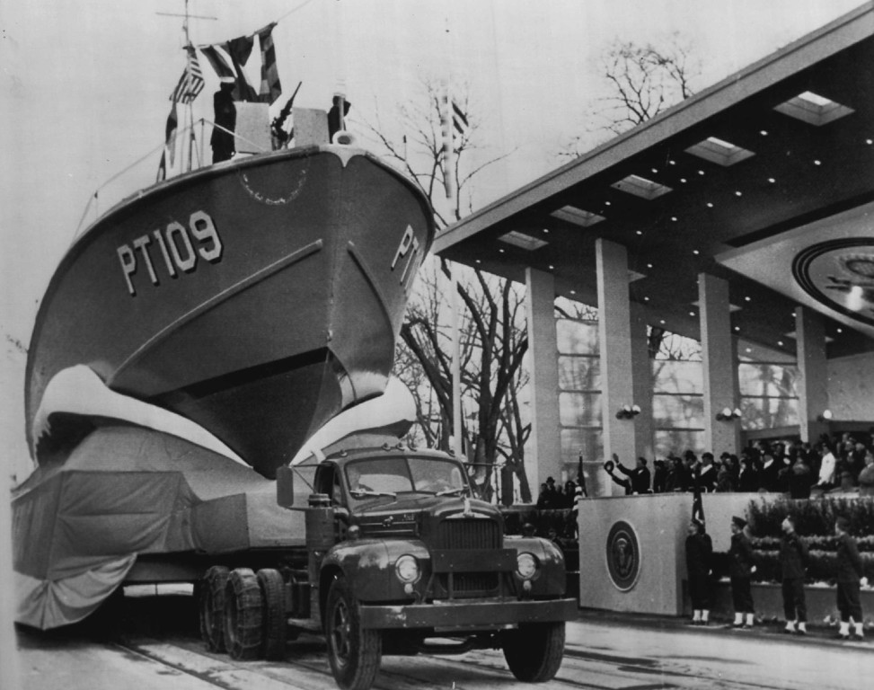 . Kennedy waves to sailors on a Navy PT boat as it rides high above Pennsylvania Avenue during the inaugural parade Jan. 25, 1961. Kennedy commanded such a vessel during World War 11 when it was rammed by a Japanese destroyer. Denver Post file