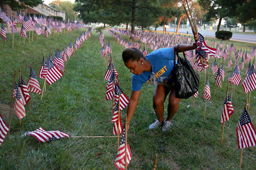. Crystal Eubanks, a JROTC student at Beaumont High School, stands up flags outside the school on Wednesday, Sept. 11, 2013, in St. Louis.  On Tuesday night, ROTC students put up about 3,000 flags as tribute to the people who lost their lives in the attacks of Sept. 11, 2001.  Wednesday marked the 12th anniversary of the 9/11 terrorist attacks. (AP Photo/St. Louis Post-Dispatch,  David Carson)