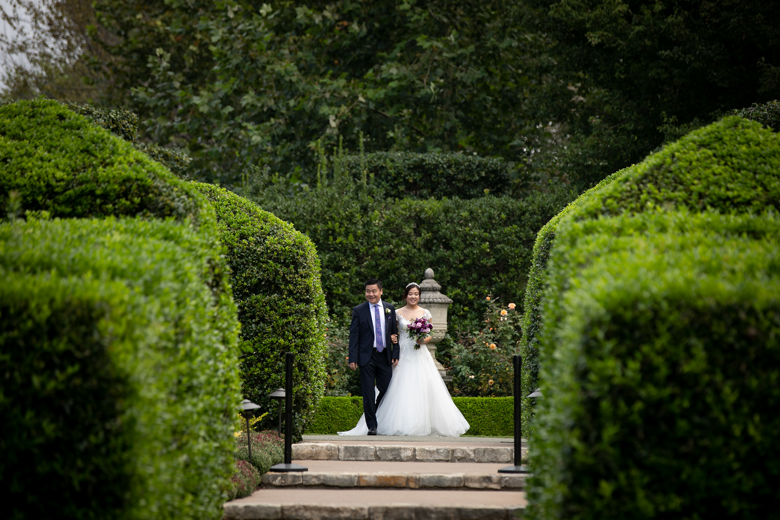 a man walks his daughter down the aisle through green hedges and gardens