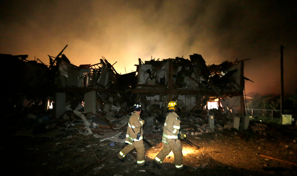 . Firefighters check a destroyed apartment complex near the fertilizer plant that exploded earlier in West, Texas, in this photo made early Thursday, April 18, 2013.  (AP Photo/LM Otero)