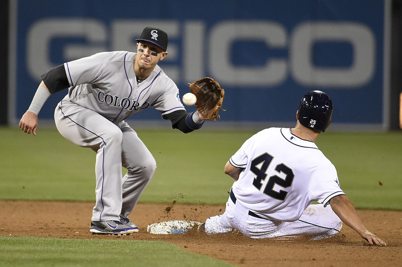 . SAN DIEGO, CA - APRIL 15:  Troy Tulowitzki of the Colorado Rockies tags out Will Venable of the San Diego Padres as he tries to steal second base during the fifth inning of a  baseball game at Petco Park April 15, 2014 in San Diego, California. All uniformed team members are wearing jersey number 42 in honor of Jackie Robinson Day. (Photo by Denis Poroy/Getty Images)