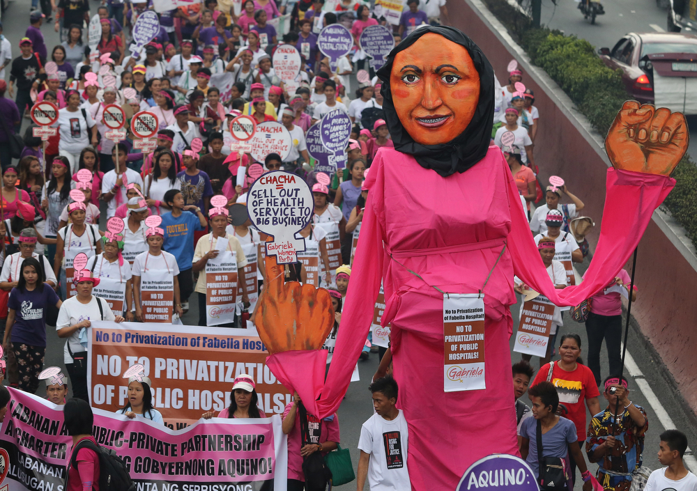 . An effigy of a woman is carried by activists as they march towards the Malacanang Palace to mark International Women\'s Day in Manila, Philippines on Saturday, March 8, 2014. The group are blaming Philippine President Benigno Aquino III who they alleged to have neglected women and their families. (AP Photo/Aaron Favila)