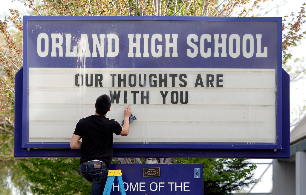 . Sergio Parra, 16, a 10th grader at Orland High School, cleans the glass on the school\'s sign, Friday, April 11, 2014, after placing a memorial remembering the victims of a fiery crash between a tour bus and a FedEx truck in Orland, Calif.  Ten people were killed and dozens injured in the fiery crash that happened Thursday, between the truck and a bus carrying high school students on a visit to a Northern California college.  Orland High is across the street from where a Red Cross shelter was setup to handle some of survivors of the accident. (AP Photo/Rich Pedroncelli)