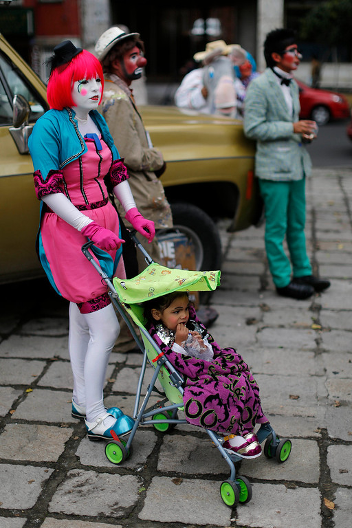 . Clowns wait for the start of a laugh-a-thon on the third day of activities at the 17th International Clown Convention in Mexico City, Wednesday, Oct. 23, 2013. They sought a world laugh record but no Guinness official was seen present and they fell short of 15 minutes. (AP Photo/Dario Lopez-Mills)