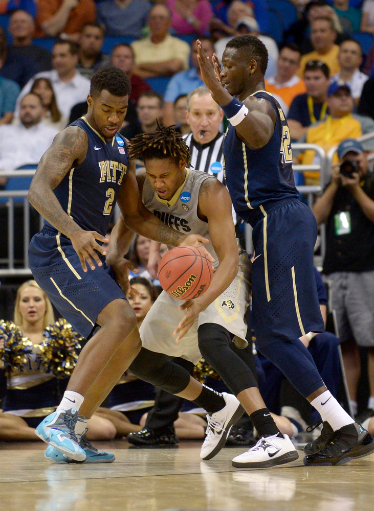 . Pittsburgh forwards Michael Young (2), left, and Talib Zanna (42), right,  defend Colorado forward Xavier Johnson (2) as he loses control of the ball during the first half in a second-round game in the NCAA college basketball tournament Thursday, March 20, 2014, in Orlando, Fla. (AP Photo/Phelan M. Ebenhack)