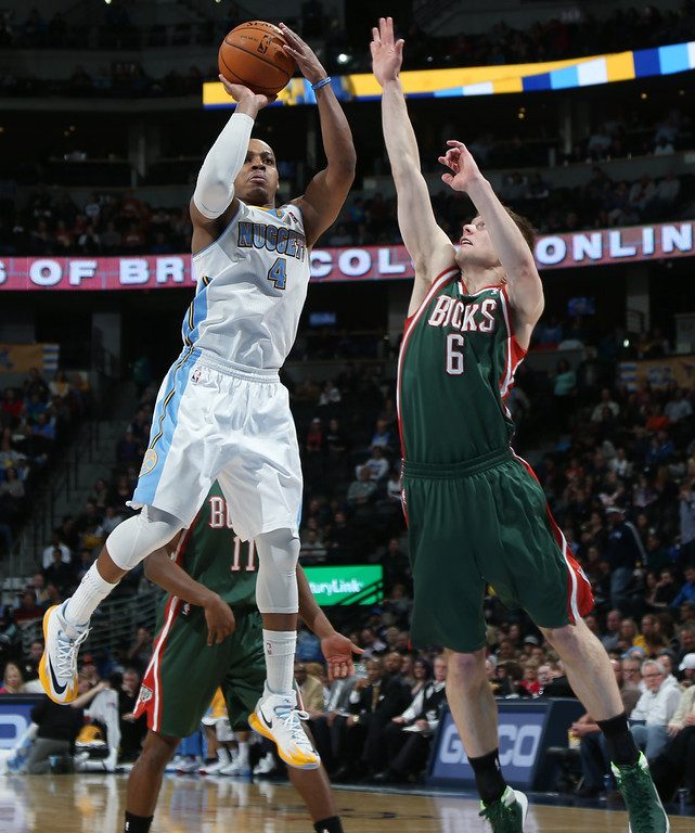 . Denver Nuggets guard Randy Foye, left, goes up to shoot as Milwaukee Bucks guard Nate Wolters covers in the third quarter of the Nuggets\' 110-100 victory in an NBA basketball game in Denver, Wednesday, Feb. 5, 2014. (AP Photo/David Zalubowski)