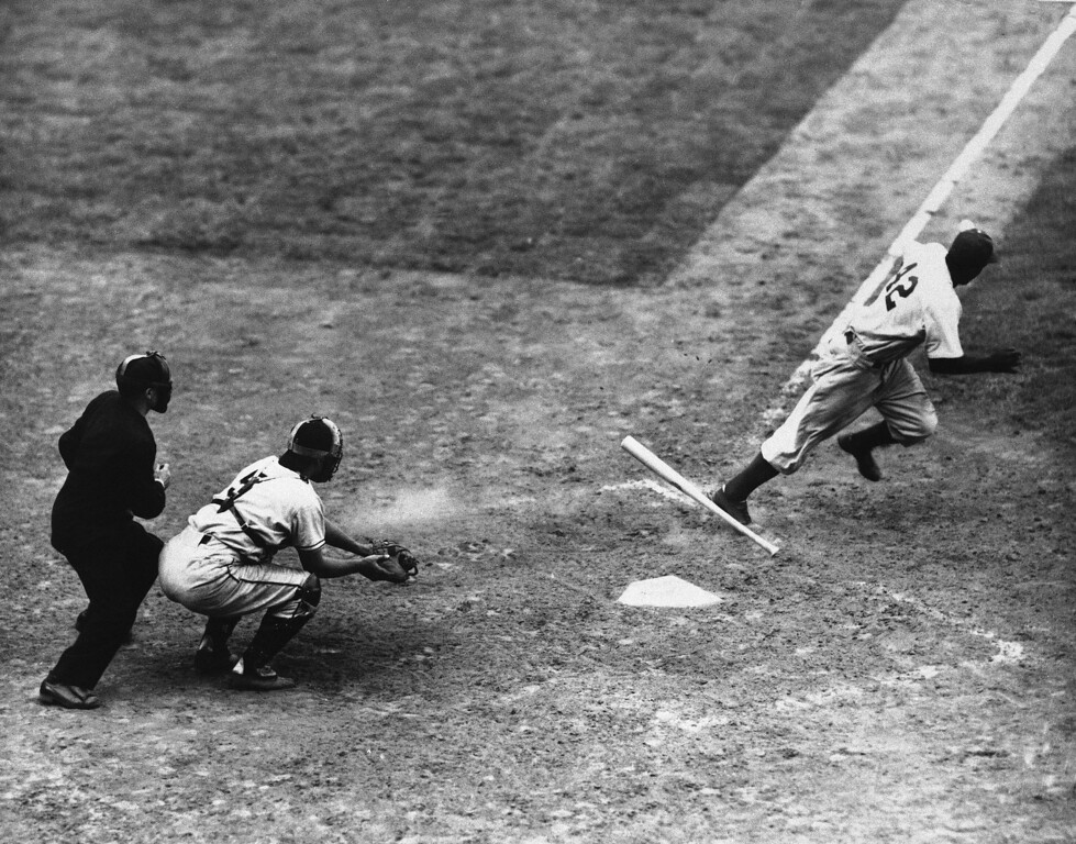. The Dodgers\' Jackie Robinson drops bat and takes off for first after bunting safely in the fifth inning of the game with the Giants at Ebbets Field, July 3, 1947 in New York.  (AP Photo)
