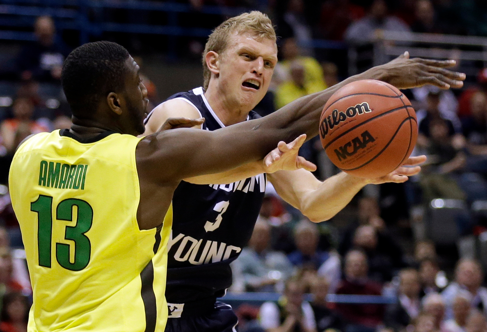 . BYU guard Tyler Haws (3) passes the ball against Oregon forward Richard Amardi (13) during the second half of a second-round game in the NCAA college basketball tournament Thursday, March 20, 2014, in Milwaukee. (AP Photo/Jeffrey Phelps)