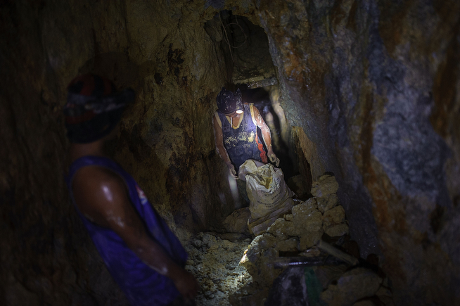 . A gold miner tests the weight of a sack full of raw ore before carrying it to a processing station on the surface, on April 22, 2014 in Pinut-An, Philippines. (Photo by Luc Forsyth/Getty Images)