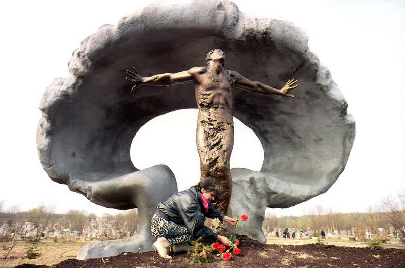 . A woman puts flowers at the new memorial to victims of the 1986 Chernobyl nuclear power plant explosion at Mitino cemetery 27 April 1993. The memorial was opened 26 April on the seventh anniversary of the Chernobyl disaster, which killed an initial 31 people, according to Soviet officials, and sent a cloud of radiation over Europe. (Photo credit should read ERIC FEFERBERG/AFP/Getty Images)