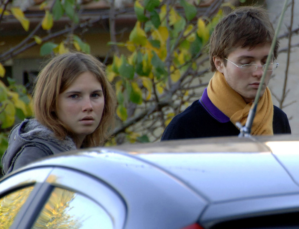 . This photo taken Friday Nov. 2, 2007, and made available on Thursday Nov. 8, 2007 shows Amanda Marie Knox, left, and Raffaele Sollecito, looking on outside the rented house where 21-year-old British student Meredith Kercher was found dead Friday, in Perugia, Italy. (AP Photo/Stefano Medici)