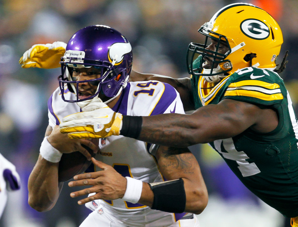 . Green Bay Packers outside linebacker Dezman Moses, right, tackles Minnesota Vikings quarterback Joe Webb (14) during the first half of an NFL wild card playoff football game Saturday, Jan. 5, 2013, in Green Bay, Wis. (AP Photo/Mike Roemer)