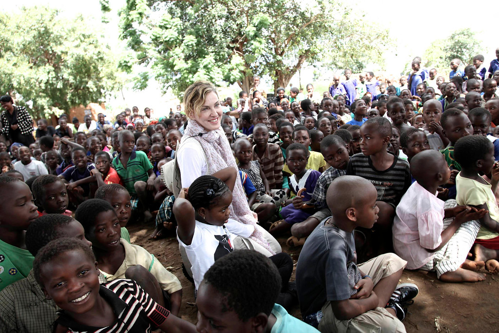 . This image released by Liz Rosenberg Media shows singer Madonna visiting school children in Chorwe, Malawi on Wednesday, April 3, 2013. Madonna�s foundation, Raising Malawi, has built ten schools in partnership with BuildOn which are currently educating over 4,000 students per year. (AP Photo/Liz Rosenberg Media)