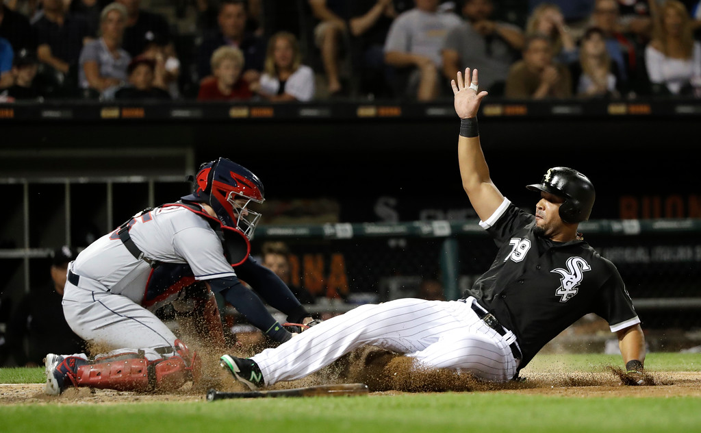. Chicago White Sox\'s Jose Abreu, right, avoids the tag of Cleveland Indians catcher Roberto Perez and scores on a single by Kevan Smith during the sixth inning of a baseball game Wednesday, June 13, 2018, in Chicago. (AP Photo/Charles Rex Arbogast)
