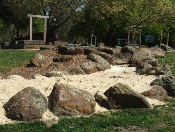 naturalistic sandpit with boulder edging