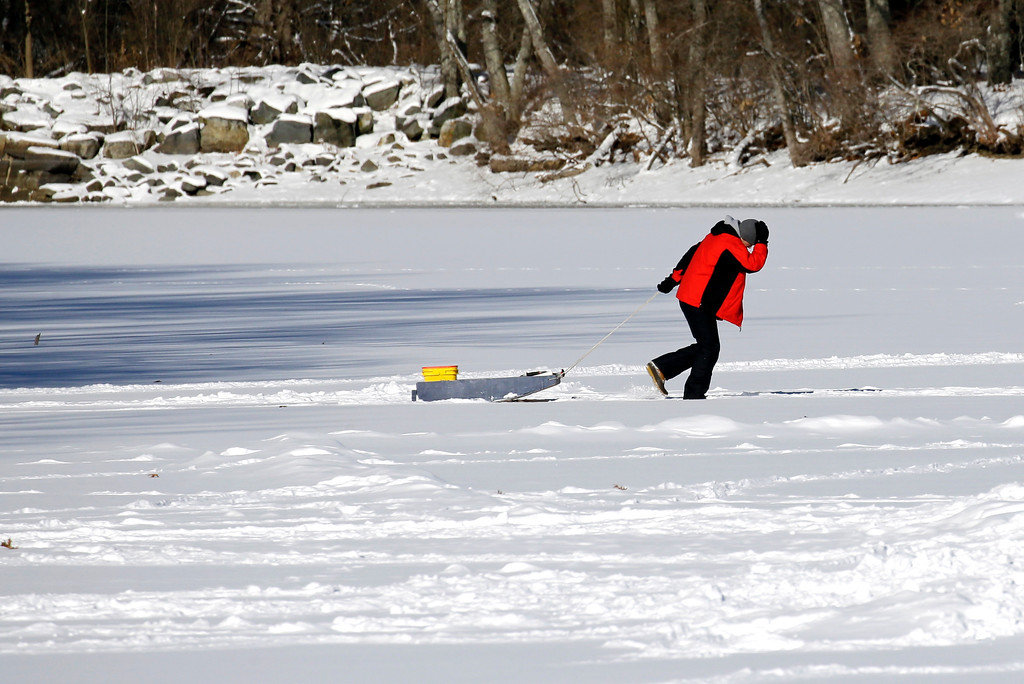 . An ice fisherman drags his gear out onto Lake Cochichewick, Monday, Jan. 9, 2017, in North Andover, Mass. As the East Coast waits to thaw out from a weekend icy mess, another storm is bringing rain and the potential of the worst flooding in more than a decade to the West coast. (AP Photo/Elise Amendola)