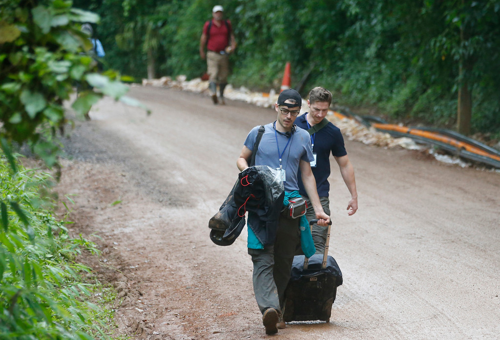 . Media staff leave the area around the entrance of the cave where 12 boys and their soccer coach have been trapped for two weeks, in Mae Sai, Chiang Rai province, in northern Thailand Sunday, July 8, 2018. Thai authorities asked media to leave the area, fueling speculation on Sunday morning that a rescue mission could be imminent. (AP Photo/Sakchai Lalit)