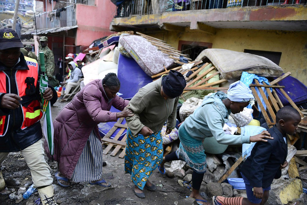 . Residents walk past the rubble of a collapsed building in Nairobi as rescue efforts continue on April 30, 2016.  / AFP PHOTO / JOHN MUCHUCHA/AFP/Getty Images