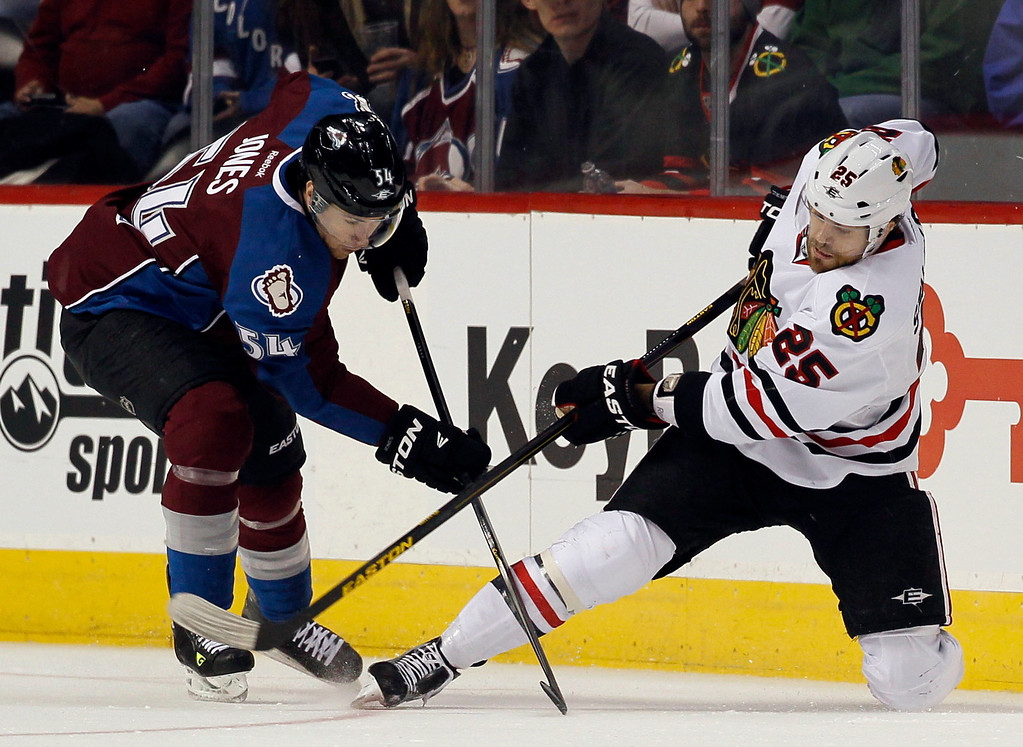 . Chicago Blackhawks right wing Viktor Stalberg, right, of Sweden, clears the puck from along the boards as Colorado Avalanche right wing David Jones covers in the first period of an NHL hockey game in Denver, Friday, March 8, 2013. (AP Photo/David Zalubowski)